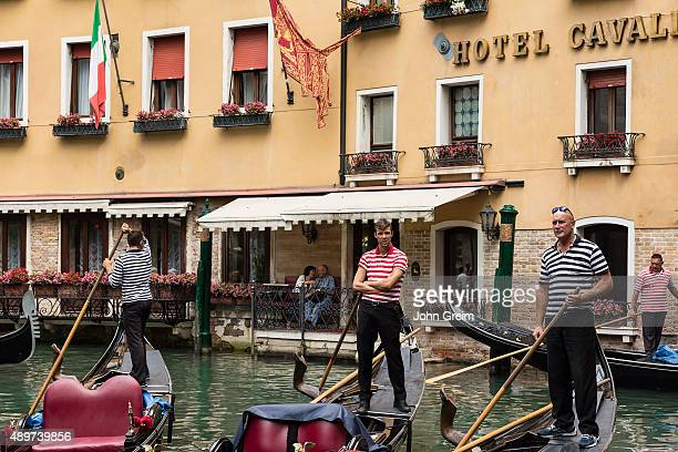 Gondoliers navigate waiting for customers