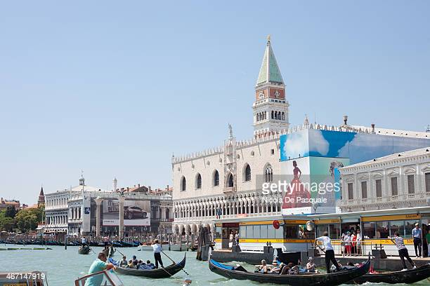 CONTENT] Gondoliers riding gondolas on Grand Canal and showing Venice to group of tourists St Mark Square and Tower on background