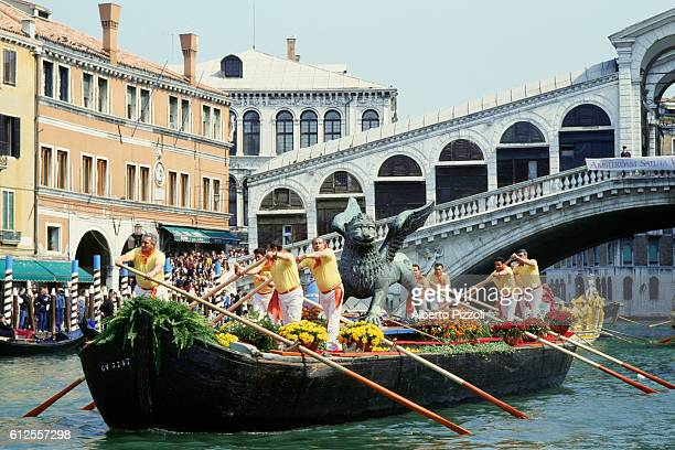 Gondoliers transport a statue of a winged lion to St. Mark's Square during a ceremony in Venice.