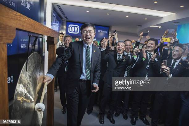 Gong Yu founder and chief executive officer of iQiyicom hits a ceremonial gong during the company's initial public offering at the Nasdaq MarketSite...