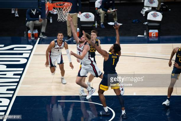 Gonzaga Bulldogs forward Drew Timme drives between West Virginia Mountaineers guard Sean McNeil and West Virginia Mountaineers forward Derek Culver...