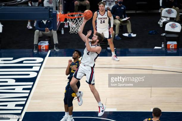 Gonzaga Bulldogs forward Drew Timme drives by West Virginia Mountaineers guard Taz Sherman for a layup during the men's Jimmy V Classic college...