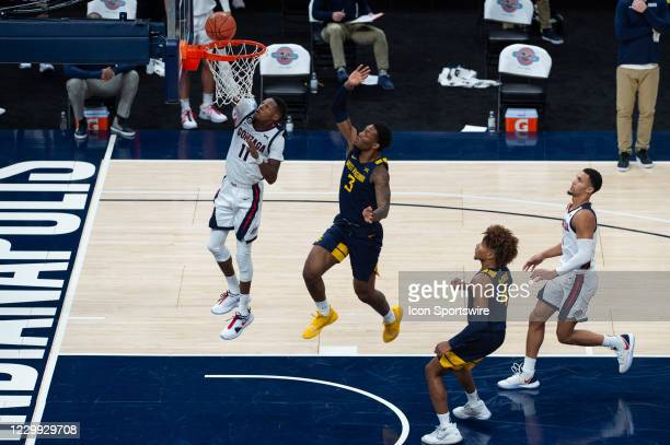 Gonzaga Bulldogs guard Joel Ayayi drives past West Virginia Mountaineers forward Gabe Osabuohien for a layup during the men's Jimmy V Classic college...