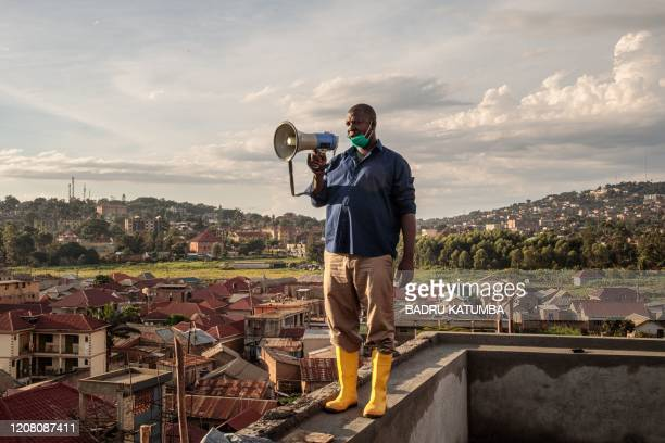 TOPSHOT Gonzaga Yiga a 49yearold community chairperson appeals to residents through a speaker from the tallest building of the area in morning and...
