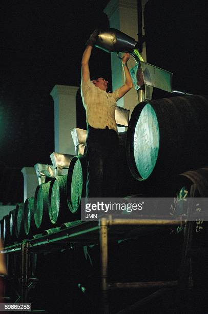 Gonzalez Byass wine cellars A man throws sherry from a jar to a barrel in the cellars of the Gonzalez Byass Company