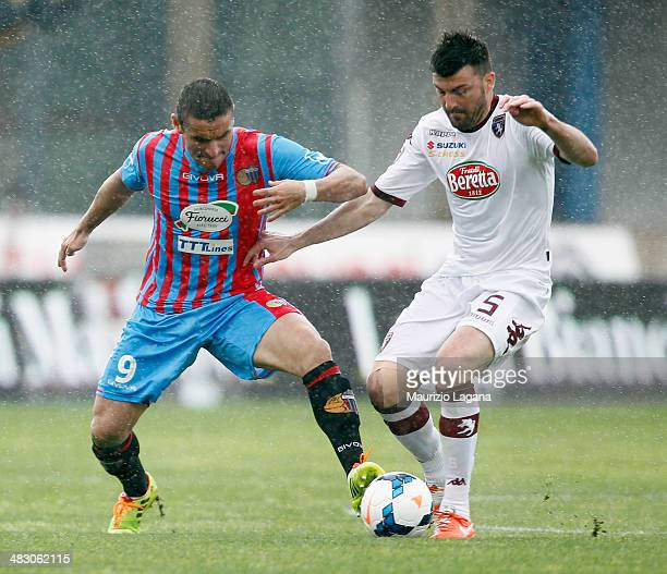 Gonzalo Bergessio of Catania competes for the ball with Cesare Bovo of Torino during the Serie A match between Calcio Catania and Torino FC at Stadio...