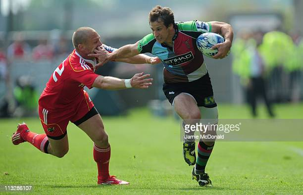 Gonzalo Camachio of Harlequins slips the tackle of Paul Warwick of Munster during the Amlin Cup semi-final match between Munster and Harlequins at...