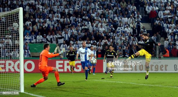 Gonzalo Castro of Dortmund scores his team's opening goal against goalkeeper Alexander Brunst of Magdeburg during the DFB Cup match between 1 FC...