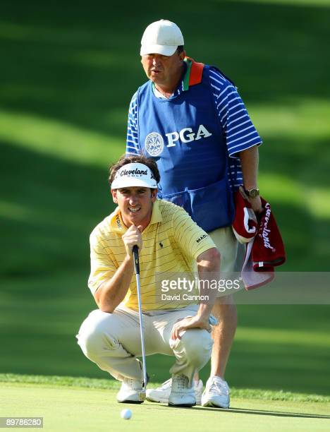 Gonzalo Fernandez-Castano of Spain lines up his putt on the seventh hole with the help of his caddie Jeff Paul during the second round of the 91st...