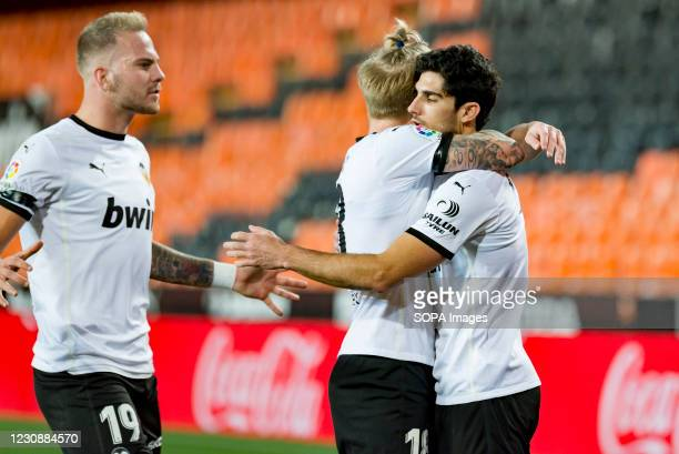Gonzalo Guedes, Uros Racic and Daniel Wass of Valencia celebrating a goal during the Spanish La Liga football match between Valencia and Elche at...