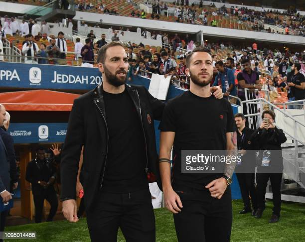 Gonzalo Higuain and Andrea Bertolacci of AC Milan walk on pitch prior to the Italian Supercup match between Juventus and AC Milan at King Abdullah...
