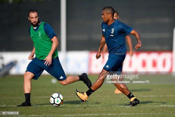 Gonzalo Higuain and Douglas Costa of Juventus during a training session on August 7 2017 in Vinovo Italy
