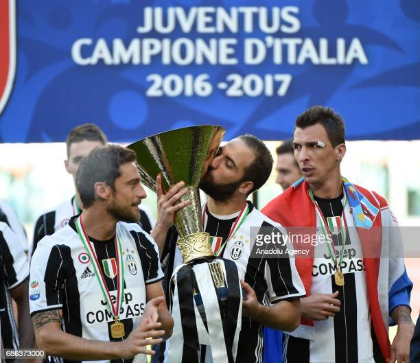 Gonzalo Higuain Claudio Marchisio and Mario Manzdukic of Juventus celebrate the Italian Serie A championship with the trophy after winning the...