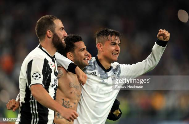 Gonzalo Higuain Dani Alves and Paulo Dybala of Juventus celebrate victory following the UEFA Champions League Semi Final second leg match between...