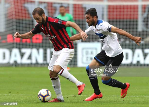 Gonzalo Higuain of AC Milan competes for the ball with Jose Luis Palomino of Atalanta BC during the Serie A match between AC Milan and Atalanta BC at...