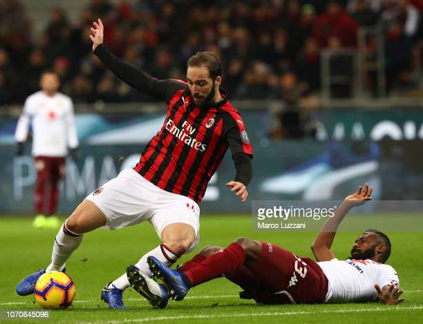 Gonzalo Higuain of AC Milan competes for the ball with Nicolas Nkoulou of Torino FC during the Serie A match between AC Milan and Torino FC at Stadio...