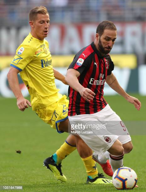 Gonzalo Higuain of AC Milan competes for the ball with Valter Birsa of Chievo Verona during the Serie A match between AC Milan and Chievo Verona at...