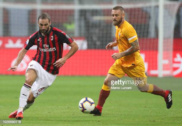 Gonzalo Higuain of AC Milan is challenged by Daniele De Rossi of AS Roma during the serie A match between AC Milan and AS Roma at Stadio Giuseppe...