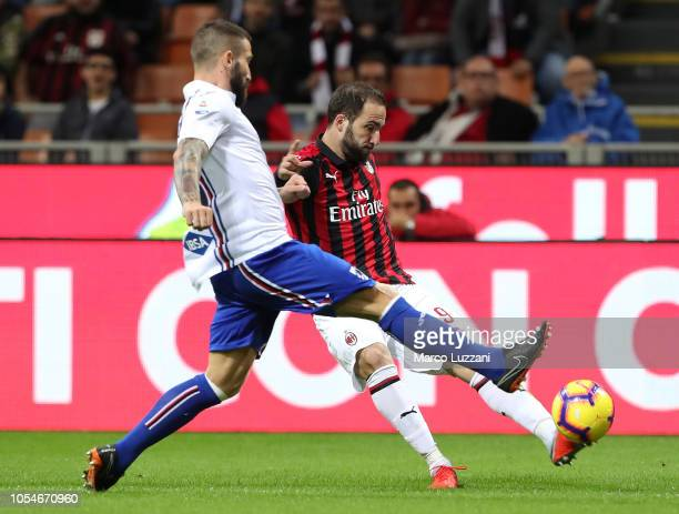 Gonzalo Higuain of AC Milan is challenged by Lorenzo Tonelli of UC Sampdoria during the Serie A match between AC Milan and UC Sampdoria at Stadio...