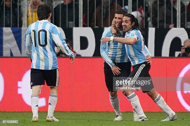 Gonzalo Higuain of Argentina celebrates the first goal with Jonás Gutiérrez of Argentina and Lionel Messi during the International Friendly match...