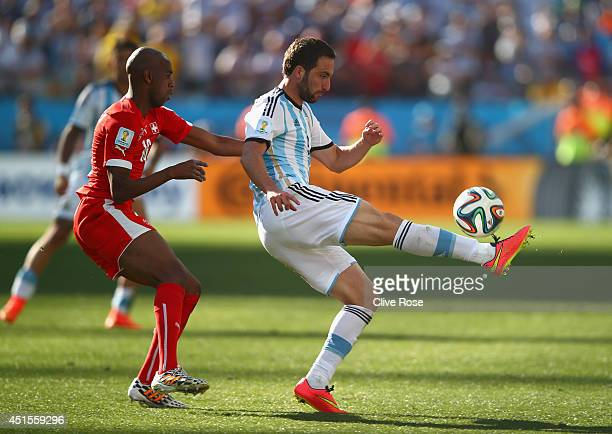 Gonzalo Higuain of Argentina controls the ball as Gelson Fernandes of Switzerland gives chase during the 2014 FIFA World Cup Brazil Round of 16 match...
