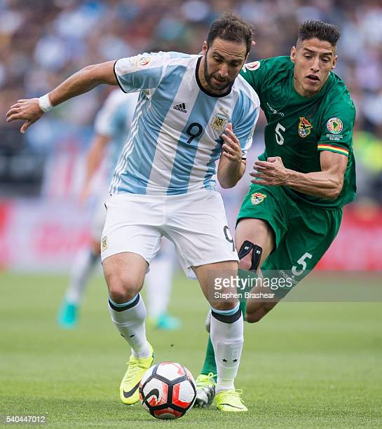 Gonzalo Higuain of Argentina dribbles the ball as Nelson Cabrera of Bolivia defends during a group D match between Argentina and Bolivia at...