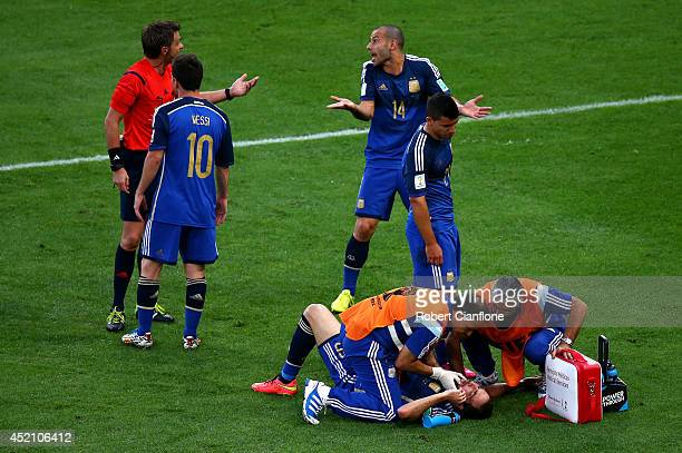 Gonzalo Higuain of Argentina receives treatment as teammates Lionel Messi Sergio Aguero and Javier Mascherano appeal to referee Nicola Rizzoli during...