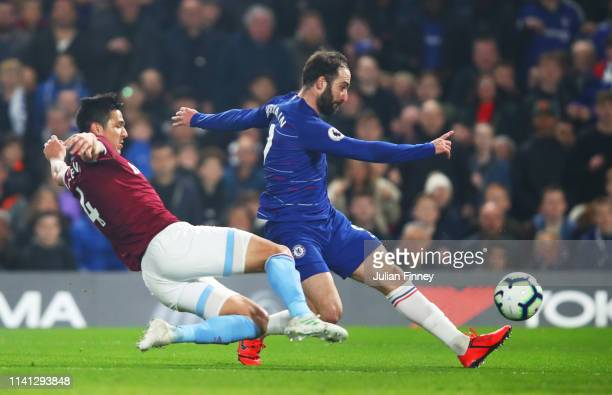 Gonzalo Higuain of Chelsea shoots as Fabian Balbuena of West Ham United challenges during the Premier League match between Chelsea FC and West Ham...