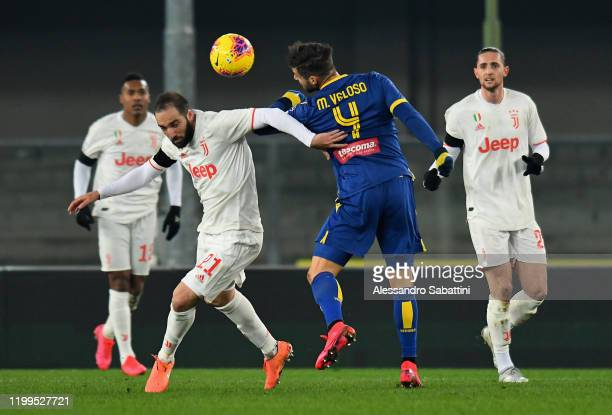 Gonzalo Higuain of Juventus competes for the ball with Miguel Veloso of Hellas Verona during the Serie A match between Hellas Verona and Juventus at...