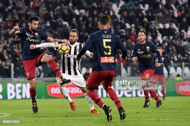 Gonzalo Higuain of Juventus competes for the ball with Nicolas Spolli and Armando Izzo of Genoa CFC during the Serie A match between Juventus and...