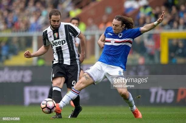 Gonzalo Higuain of Juventus FC and Edgar Barreto of UC Sampdoria compete for the ball during the Serie A football match between UC Sampdoria and...