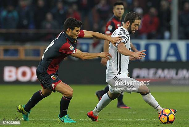 Gonzalo Higuain of Juventus FC competes for the ball with Ezequiel Munoz of Genoa CFC during the Serie A match between Genoa CFC and Juventus FC at...