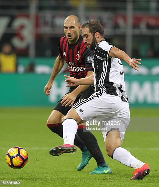 Gonzalo Higuain of Juventus FC competes for the ball with Gabriel Paletta of AC Milan during the Serie A match between AC Milan and Juventus FC at...