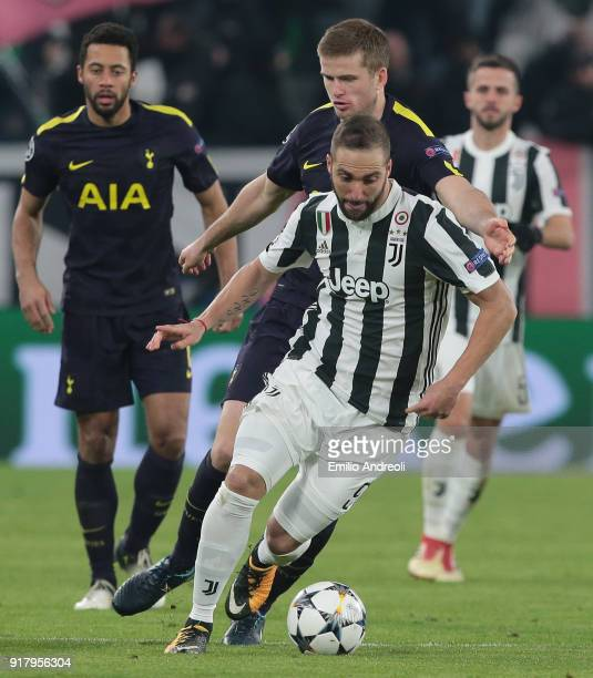Gonzalo Higuain of Juventus FC is challenged by Eric Dier of Tottenham Hotspur during the UEFA Champions League Round of 16 First Leg match between...