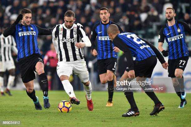 Gonzalo Higuain of Juventus in action between Roberto Gagliardini and Joao Miranda of FC Internazionale during the Serie A match between Juventus and...