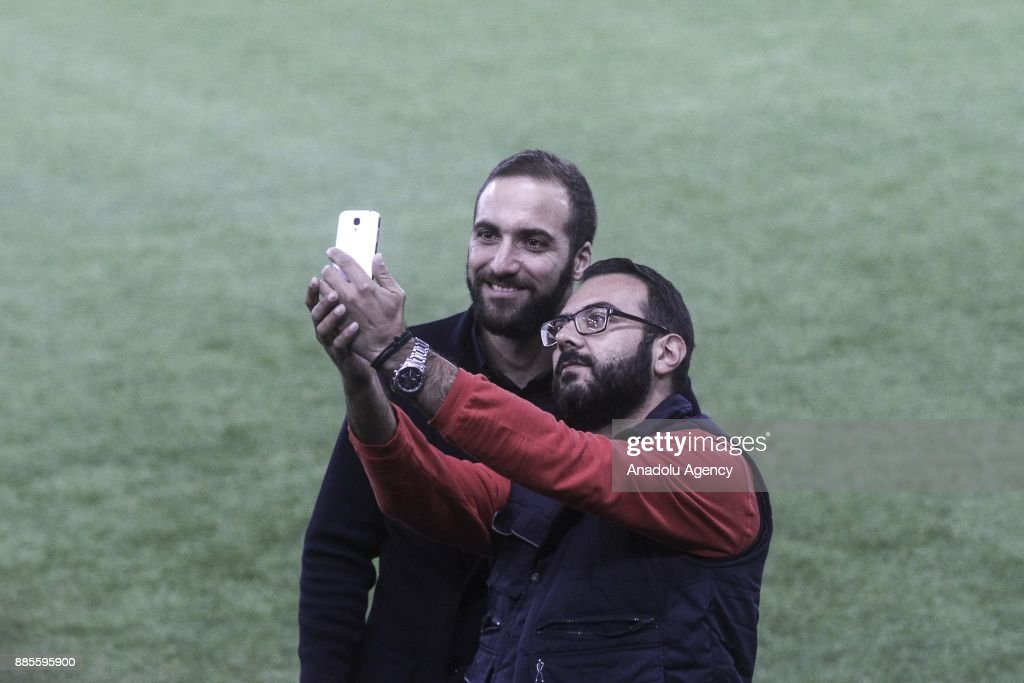 Gonzalo Higuain (L) of Juventus poses for a photo with a fan as he inspects the pitch ahead of the UEFA Champions League soccer match between Olympiacos F.C. and Juventus at Georgios Karaiskakis Stadium in Athens, Greece on December 04, 2017.