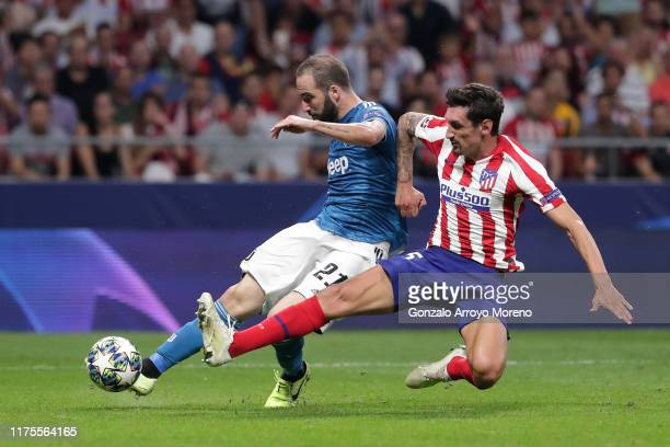 Gonzalo Higuain of Juventus shoots under pressure from Stefan Savic of Atletico Madrid during the UEFA Champions League group D match between...
