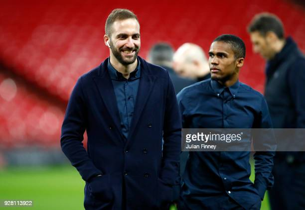 Gonzalo Higuain of Juventus speaks to Douglas Costa of Juventus on the pitch prior to the Juventus press conference at Wembley Stadium on March 6...