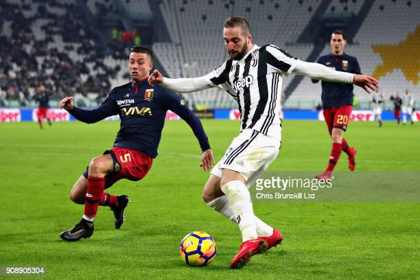 Gonzalo Higuain of Juventus takes a shot as Armando Izzo of Genoa CFC attempts to block during the Serie A match between Juventus and Genoa CFC at...