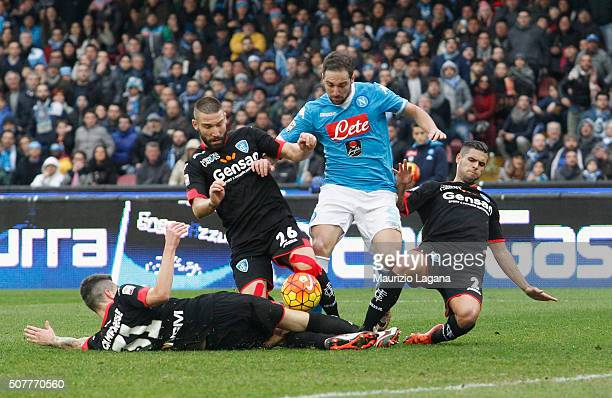 Gonzalo Higuain of Napoli competes for the ball with Michel Camporese Lorenzo Tonelli and Vincent Laurini of Empoli during the Serie A match between...