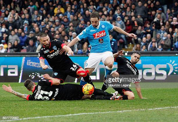 Gonzalo Higuain of Napoli competes for the ball with Michele Camporese Lorenzo Tonelli and Vincent Laurini of Empoli during the Serie A match between...
