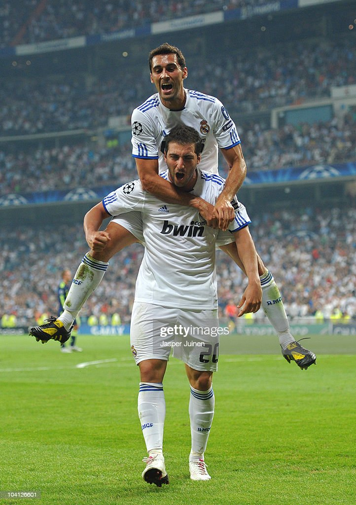 Gonzalo Higuain of Real Madrid celebrates scoring his sides second goal with his teammate Alvaro Arbeloa (Top) during the UEFA Champions League group G match between Real Madrid and Ajax at the Estadio Santiago Bernabeu on September 15, 2010 in Madrid, Spain.