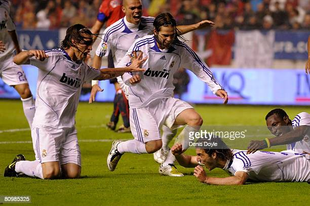 Gonzalo Higuain of Real Madrid celebrates with Sergio Ramos and Gago after scoring Real's second goal during the La Liga match between Osasuna and...
