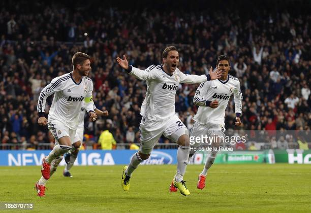 Gonzalo Higuain of Real Madrid celebrates with teammates Sergio Ramos and Raphael Varane after scoring their team's third goal during the UEFA...