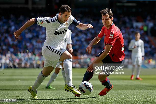 Gonzalo Higuain of Real Madrid CF competes for the ball with Unai Garcia of CA Osasuna during the La Liga match between Real Madrid CF and CA Osasuna...
