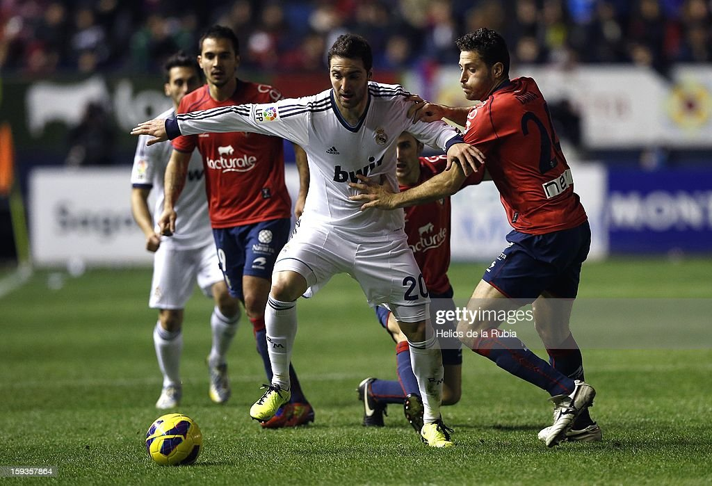 Gonzalo Higuain of Real Madrid CF duels for the ball with Damia Abella of CA Osasuna during the La Liga match between CA Osasuna and Real Madrid CF at Estadio Reyno de Navarra on January 12, 2013 in Pamplona, Spain.