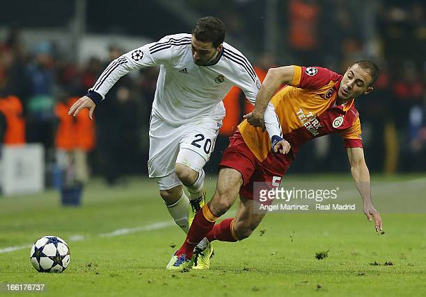 Gonzalo Higuain of Real Madrid is challenged by Nordin Amrabat of Galatasaray during the UEFA Champions League quarterfinal second leg match between...