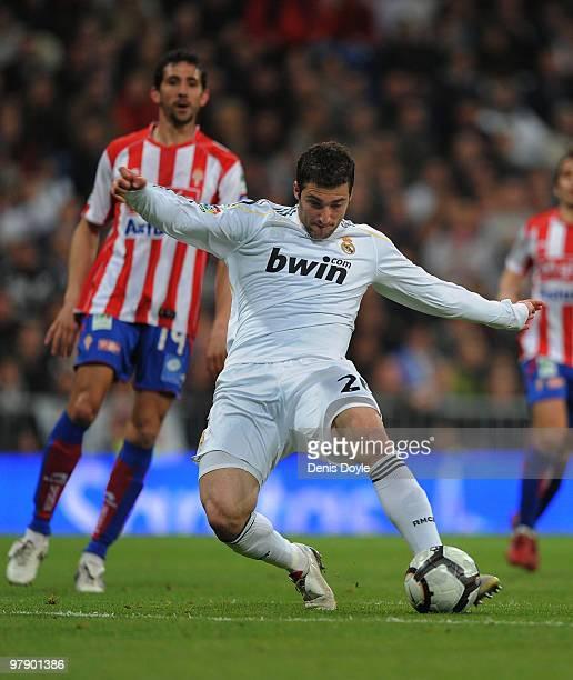 Gonzalo Higuain of Real Madrid scores Real's third goal during the La Liga match between Real Madrid and Sporting Gijon at Estadio Santiago Bernabeu...