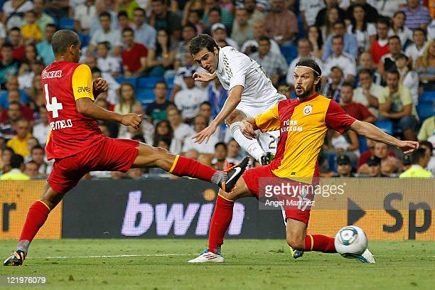 Gonzalo Higuain of Real Madrid shoots on goal between Tomas Ujfalusi and Felipe Melo of Galatasaray during the Santiago Bernabeu Trophy match between...