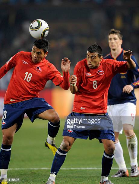 Gonzalo Jara of Chile heads the ball as teammate Arturo Vidal looks on during the 2010 FIFA World Cup South Africa Group H match between Chile and...